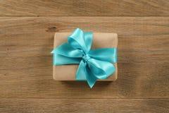 Καφετί κιβώτιο δώρων με το ανοικτό μπλε τόξο κορδελλών στον ξύλινο δρύινο πίνακα άνωθεν Στοκ Εικόνες