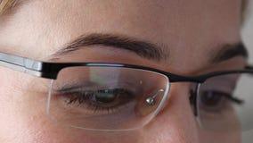 Καφετί μάτι γυναικών κινηματογραφήσεων σε πρώτο πλάνο στα γυαλιά Γυναίκα που χρησιμοποιεί ένα smartphone 4K απόθεμα βίντεο