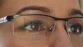 Καφετί μάτι γυναικών κινηματογραφήσεων σε πρώτο πλάνο στα γυαλιά Γυναίκα που χρησιμοποιεί ένα smartphone 4K φιλμ μικρού μήκους