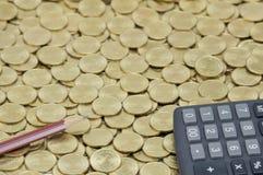 Καφετί μολύβι με το μαύρο υπολογιστή στο σωρό των χρυσών νομισμάτων Στοκ Φωτογραφία
