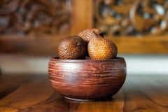 Καφετί ξύλινο κύπελλο με τα φρούτα salak ή φιδιών από το Μπαλί, Ινδονησία Χαράζοντας ξύλινο υπόβαθρο στοκ φωτογραφία με δικαίωμα ελεύθερης χρήσης