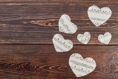 Καφετί ξύλινο υπόβαθρο με τις καρδιές εγγράφου Στοκ Εικόνες