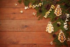 Καφετί ξύλινο υπόβαθρο με το σχέδιο Χριστουγέννων με τους κομψούς κλάδους, τους κώνους πεύκων και τα μπισκότα Στοκ φωτογραφία με δικαίωμα ελεύθερης χρήσης