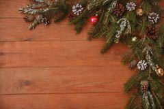 Καφετί ξύλινο υπόβαθρο με το σχέδιο Χριστουγέννων με τους κομψούς κλάδους, τους κώνους πεύκων και τα παιχνίδια γυαλιού Χριστουγέν Στοκ Φωτογραφία