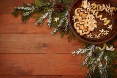 Καφετί ξύλινο υπόβαθρο με το σχέδιο Χριστουγέννων με τους κομψούς κλάδους, τους κώνους πεύκων και τα μπισκότα Στοκ Φωτογραφία