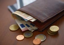 Καφετί πορτοφόλι με τα ευρο- χρήματα εσωτερικά και τα νομίσματα, πιστωτικές κάρτες πλησίον Στοκ Εικόνα