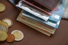 Καφετί πορτοφόλι με τα ευρο- χρήματα εσωτερικά και τα νομίσματα, πιστωτικές κάρτες πλησίον Στοκ Εικόνες