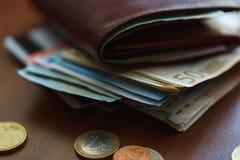 Καφετί πορτοφόλι με τα ευρο- χρήματα εσωτερικά και τα νομίσματα, πιστωτικές κάρτες πλησίον Στοκ φωτογραφία με δικαίωμα ελεύθερης χρήσης