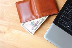 Καφετί πορτοφόλι με τα μετρητά δολαρίων και σημειωματάριο στο καθαρό ξύλινο backgro Στοκ Φωτογραφία