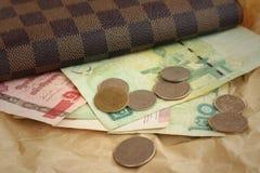 Καφετί πορτοφόλι με το μπατ της Ταϊλάνδης στο καφετί υπόβαθρο Στοκ Εικόνα