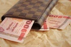 Καφετί πορτοφόλι με το μπατ της Ταϊλάνδης στο καφετί υπόβαθρο Στοκ Εικόνες