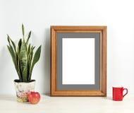 Καφετί πρότυπο πλαισίων με το δοχείο, την κούπα και το μήλο εγκαταστάσεων στο ξύλινο ράφι Στοκ Εικόνες