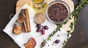 Καφετί ρύζι, μαύρο peper, σταφύλι, χορτάρια και ελαιόλαδο στον τεμαχισμό Στοκ Εικόνα