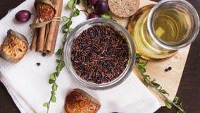 Καφετί ρύζι, σταφύλι, χορτάρια και ελαιόλαδο στο επίπεδο Λα τεμαχίζοντας πινάκων Στοκ εικόνα με δικαίωμα ελεύθερης χρήσης
