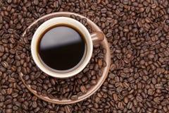 Καφετί φλυτζάνι με τον καφέ στα φασόλια καφέ από την κορυφή Στοκ Εικόνες