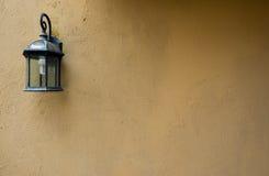 Καφετιά ακατέργαστη σύσταση συμπαγών τοίχων με τον παλαιό λαμπτήρα Στοκ Εικόνες