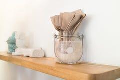 Καφετιά ανακυκλωμένη πετσέτα φραγμών στο βάζο γυαλιού στο ξύλινο ράφι στοκ εικόνες