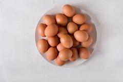 Καφετιά αυγά σε ένα άσπρο πιάτο σε ένα άσπρο υπόβαθρο Αυγά Έννοια φωτογραφιών Πάσχας Στοκ Εικόνα