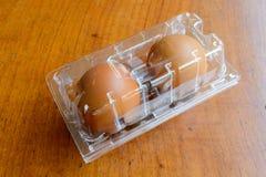 Καφετιά αυγά στο πλαστικό κιβώτιο στο ξύλινο υπόβαθρο Στοκ φωτογραφίες με δικαίωμα ελεύθερης χρήσης
