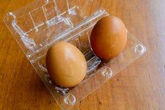Καφετιά αυγά στο πλαστικό κιβώτιο στο ξύλινο υπόβαθρο Στοκ Εικόνες