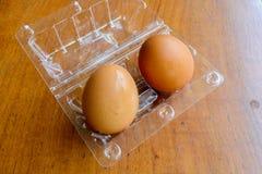 Καφετιά αυγά στο πλαστικό κιβώτιο στο ξύλινο υπόβαθρο Στοκ φωτογραφία με δικαίωμα ελεύθερης χρήσης