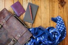 Καφετιά διαβατήριο και σημειωματάριο τσαντών δέρματος με το μπλε ναυτικό ελεγχμένο μαντίλι Στοκ Φωτογραφία