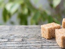 Καφετιά ζάχαρη καλάμων στο ξύλινο υπόβαθρο πράσινο δέντρο φύλλων Στοκ φωτογραφία με δικαίωμα ελεύθερης χρήσης