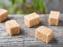 Καφετιά ζάχαρη καλάμων στο ξύλινο υπόβαθρο πράσινο δέντρο φύλλων Στοκ εικόνες με δικαίωμα ελεύθερης χρήσης