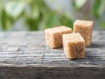 Καφετιά ζάχαρη καλάμων στο ξύλινο υπόβαθρο πράσινο δέντρο φύλλων Στοκ Εικόνες