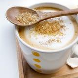Καφετιά ζάχαρη σε ένα κουτάλι και ένα φλιτζάνι του καφέ Cappuccino Στοκ Φωτογραφία