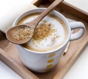 Καφετιά ζάχαρη σε ένα κουτάλι και ένα φλιτζάνι του καφέ Cappuccino Στοκ Φωτογραφίες