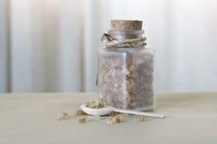Καφετιά ζάχαρη στο μπουκάλι γυαλιού και το ξύλινο κουτάλι στοκ φωτογραφίες