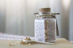 Καφετιά ζάχαρη στο μπουκάλι γυαλιού και το ξύλινο κουτάλι Στοκ εικόνα με δικαίωμα ελεύθερης χρήσης