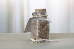 Καφετιά ζάχαρη στο μπουκάλι γυαλιού και το ξύλινο κουτάλι Στοκ Εικόνα
