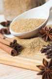 Καφετιά ζάχαρη στο ξύλινο κουτάλι με τα αρωματικά καρυκεύματα Στοκ Φωτογραφία