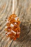 Καφετιά καραμέλα ζάχαρης βράχου κρυστάλλου στενό σε έναν επάνω ραβδιών (μακροεντολή) Στοκ φωτογραφία με δικαίωμα ελεύθερης χρήσης