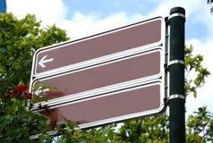 Καφετιά κενά σημάδια κατεύθυνσης με το τριαντάφυλλο και τα πράσινα δέντρα Στοκ φωτογραφία με δικαίωμα ελεύθερης χρήσης