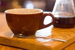 Καφετιά κεραμική κούπα καφέ με το κουτάλι ζάχαρης Στοκ εικόνα με δικαίωμα ελεύθερης χρήσης