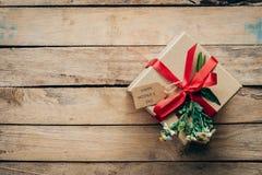 Καφετιά κιβώτιο και λουλούδι δώρων στο ξύλινο επιτραπέζιο παρόν, ημέρα μητέρων ` s ομο στοκ εικόνες