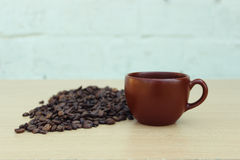 Καφετιά κινηματογράφηση σε πρώτο πλάνο κουπών καφέ με τα φασόλια καφέ σε ένα ξύλινο υπόβαθρο Στοκ Εικόνες