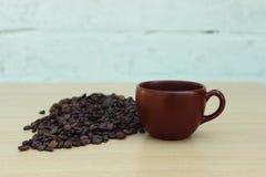 Καφετιά κινηματογράφηση σε πρώτο πλάνο κουπών καφέ με τα φασόλια καφέ σε ένα ξύλινο υπόβαθρο Στοκ φωτογραφία με δικαίωμα ελεύθερης χρήσης