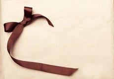 Καφετιά κορδέλλα πέρα από την εκλεκτής ποιότητας ανασκόπηση εγγράφου δώρων παλαιά Στοκ Εικόνες