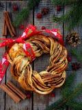 Καφετιά κουλούρια στεφανιών ζάχαρης κακάου κανέλας Γλυκό σπιτικό ψήσιμο Χριστουγέννων Ψωμί ρόλων, καρυκεύματα, διακόσμηση στο ξύλ Στοκ Εικόνες