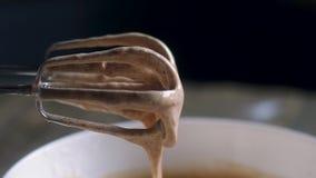 Καφετιά κρέμα με κτυπημένος σε ένα κύπελλο σιδήρου με έναν ηλεκτρικό αναμίκτη Φυσικό φως απόθεμα βίντεο