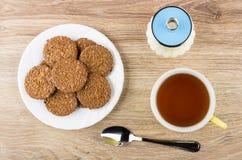 Καφετιά μπισκότα στο άσπρο πιάτο, κύπελλο ζάχαρης, φλυτζάνι του τσαγιού Στοκ Εικόνα