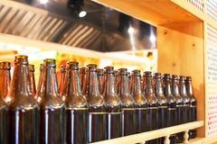 Καφετιά μπουκάλια γυαλιού της μπύρας στη σειρά στο ξύλινο ράφι, εσωτερικό σχέδιο φραγμών, έννοια δοκιμής μπύρας, ύφος νυχτερινής  στοκ εικόνες με δικαίωμα ελεύθερης χρήσης