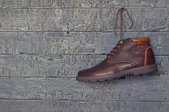 Καφετιά μπότα ατόμων ` s με το αριστερό πόδι του που κρεμά στο υπόβαθρο ενός ξύλινου τοίχου Στοκ φωτογραφία με δικαίωμα ελεύθερης χρήσης