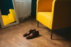 Καφετιά ξοντρά παπούτσεις παπουτσιών ατόμων ` s στο ξύλινο παρκέ πατωμάτων, δίπλα στην κίτρινους πολυθρόνα και τον καθρέφτη Στοκ φωτογραφία με δικαίωμα ελεύθερης χρήσης