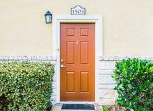 Καφετιά ξύλινη πόρτα κοντά στους πράσινους φράκτες στοκ εικόνες με δικαίωμα ελεύθερης χρήσης