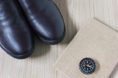 Καφετιά παπούτσια δέρματος ατόμων με το βιβλίο σημειώσεων ή ημερολόγιο με την πυξίδα Στοκ Εικόνα